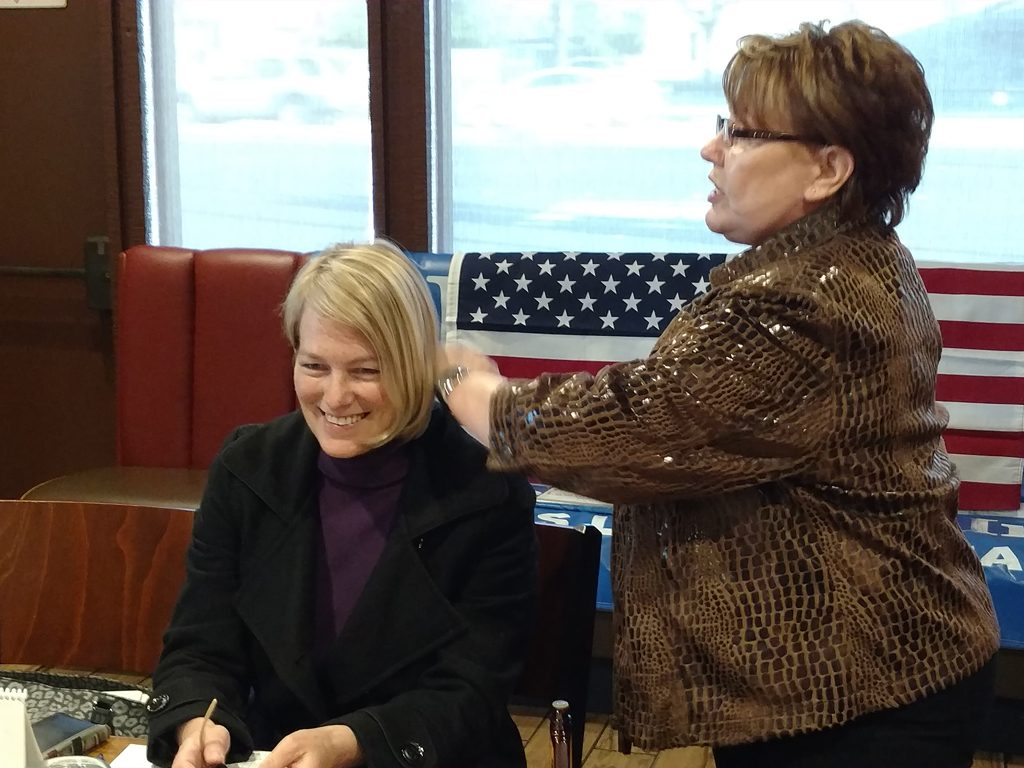 Donna Walton, our hair stylist, demonstrates a new hair product on Carol Divita.